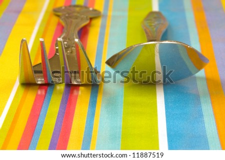 a spoon and fork on a table with reflections