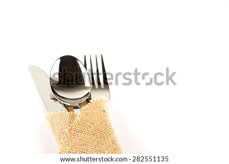 a spoon, fork and knife stacked up on a sackcloth with copy space.