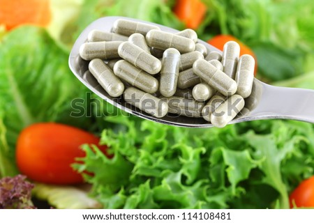 A spoon of concentrated Fiber Capsules with Fresh vegetable Salad background. Conceptual photo to choose between herbal medicine or real veggies to support Digestive system - stock photo