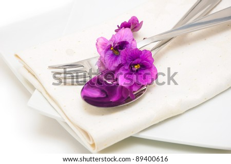 A spoon with a fork on a napkin and a plate decorated with violets - stock photo