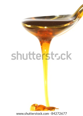 a spoon with honey ia a white background - stock photo
