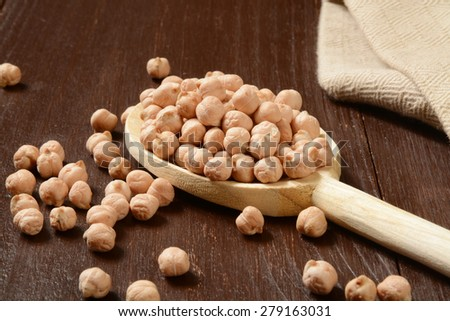 A spoonful of dried organic garbanzo beans - stock photo