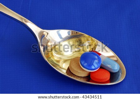 A spoonful of medicine including painkiller and vitamin  isolated on blue - stock photo