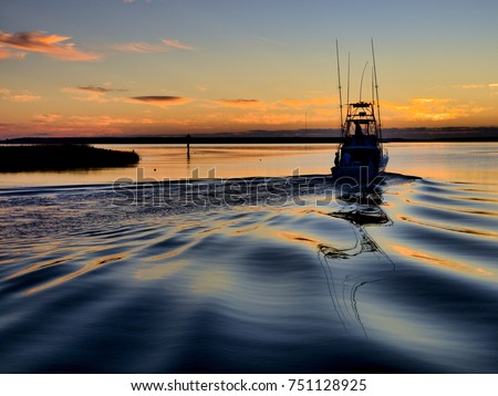 A sport fishing boat heading out of Wanchese harbor of the Outer Banks at dawn for a day of off-shore fishing.