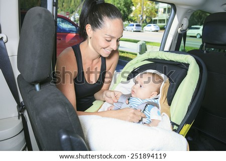 A sport woman with a baby on his car. - stock photo