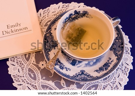 A spot of afternoon tea with a little light reading in the form of Emily Dickinson poetry. - stock photo