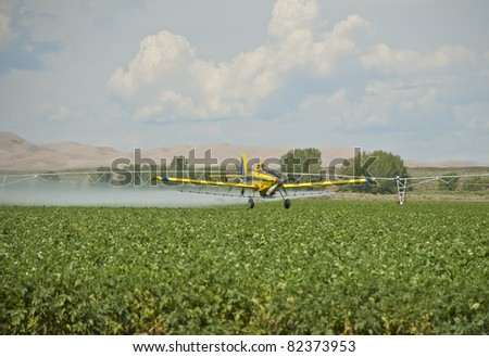 A spray plane applies chemicals to a field of potatoes on the High Desert of the Western Rockies in the USA. - stock photo
