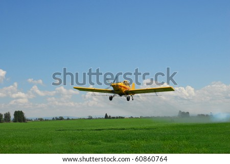 A spray plane blows smoke to check wind direction after a spray pass. - stock photo
