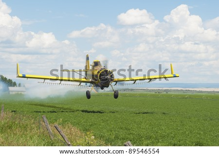 A spray-plane blows smoke to gage wind drift as it applies chemicals to an alfalfa field. - stock photo