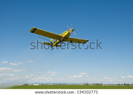 A spray plane flies over a farm and fields on the High Desert of Idaho. - stock photo