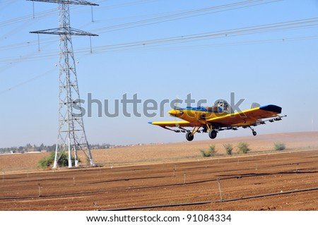 A spray plane or crop duster flies dangerously underneath electricity power lines while applying chemicals to a field of crops. - stock photo
