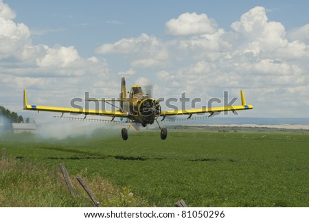 A spray plane sprays chemicals on a field of alfalfa. - stock photo