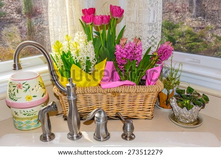 A Spring flower basket in a sunny kitchen window. - stock photo