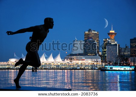A sprinter's statue in Stanley Park with background of Canada Place, Vancouver, B.C. - stock photo