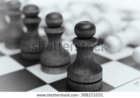 A squad of black pawns on chessboard. Figures stand in a row. Selective focus, close up view. Vintage toning. Black and white.