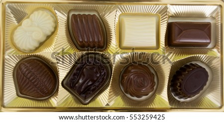 A square box of chocolates over white.