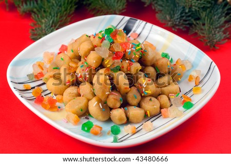 A square colorful plate of Struffoli on a red background: a typical christmas sweet of Naples, Italy. - stock photo