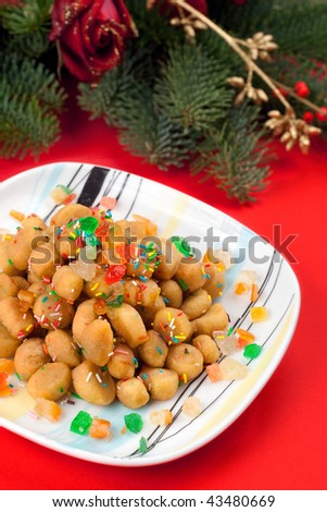 A square colorful plate of Struffoli on a red background: a typical christmas sweet of Naples, Italy.