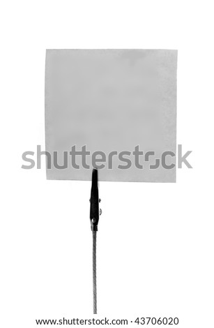 a square peice of note paper isolated on white background being held up by a paper clip.