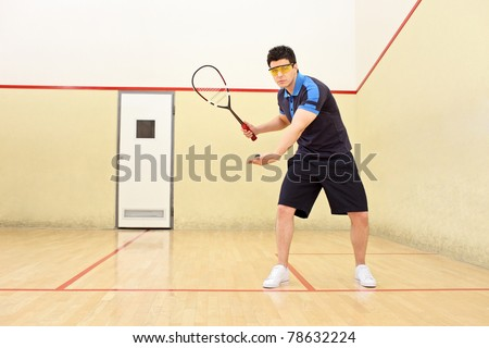A squash player serving a ball in a squash court - stock photo