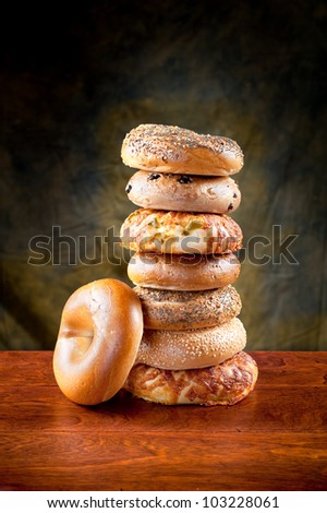 A stack of assorted, fresh, flavorful bagels on a deep, rich redwood table. - stock photo