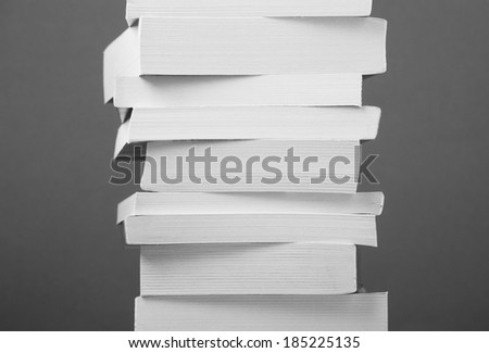A stack of assorted paperback books in black and white - stock photo