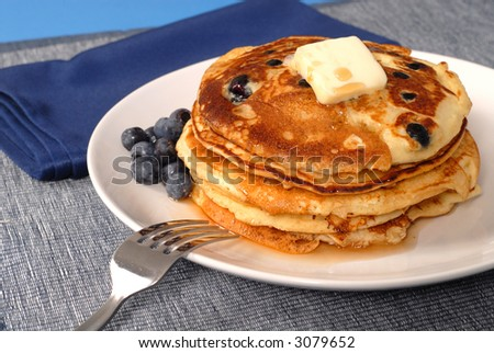 A stack of blueberry pancakes with maple syrup - stock photo