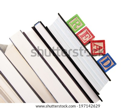 A stack of books and a child's blocks spelling read on top. - stock photo