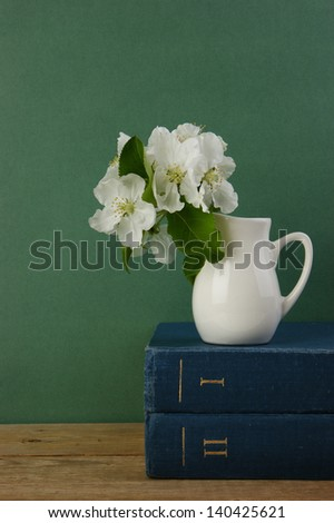 A stack of books and bird cherry branch in a jug on the wooden table - stock photo