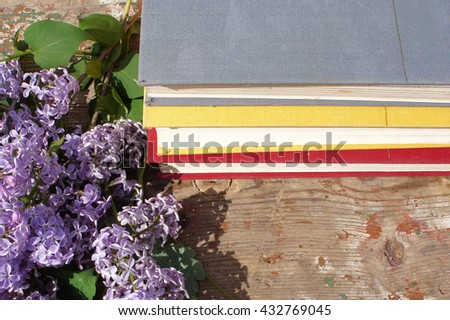 A stack of books and flowers of a lilac in the garden on wooden background.  - stock photo