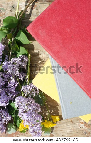 A stack of books and flowers of a lilac on wooden background. - stock photo