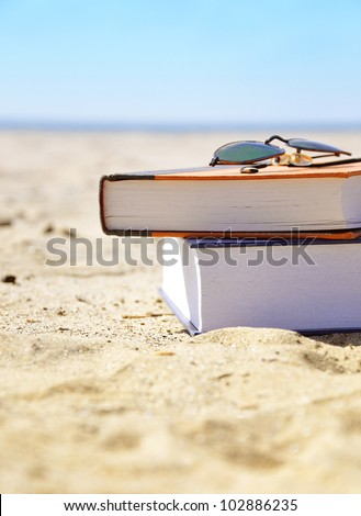 A stack of books in on the ocean sand with beach sunglasses. The water is in the background. Use it for a vacation or travel concept. - stock photo