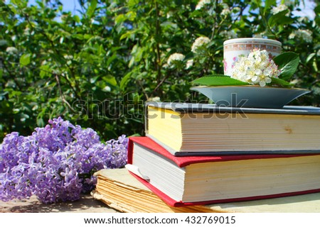 A stack of books, lilacs and Cup of tea in the garden - stock photo