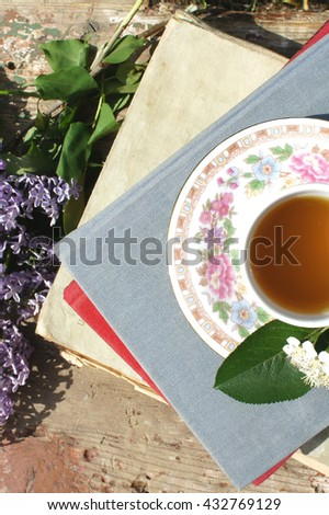 A stack of books, lilacs and Cup of tea in the garden, top view    - stock photo