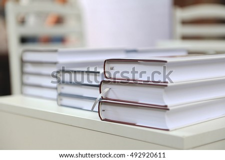 a stack of books on a white table