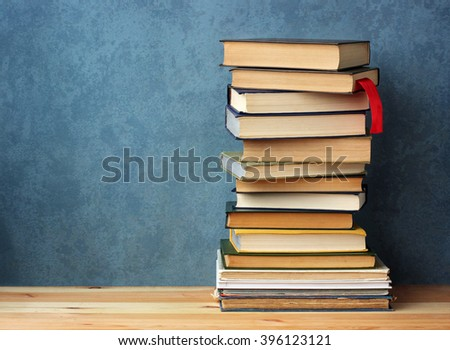 A stack of books on wooden table on blue background.