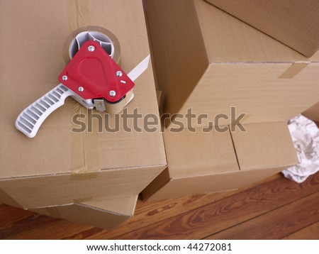 A stack of cardboard boxes and packing tape. - stock photo