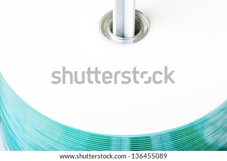 A stack of cd or dvd discs on spindle. These have large white area for your text, logo or other image placement. Shiny blueish reflections on side. - stock photo