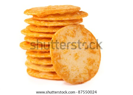 A stack of cheesy rice crackers on a white background. - stock photo