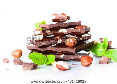 A stack of chocolate. Dark chocolate with hazelnuts on a white background.