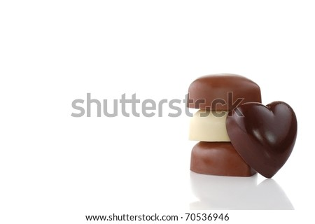 A Stack of Chocolates Behind a Heart-Shaped Chocolate with Room for Text for Valentine's Day - stock photo