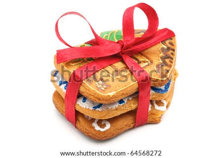 A stack of Christmas cookies in the amount of three pieces. Cookies in the shape of little houses. Pile tied a red ribbon. Painted and baked cookies manually. Isolated on white background.