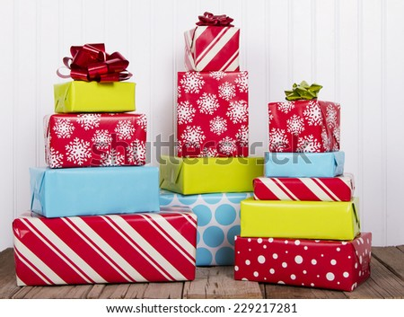 A stack of Christmas presents on rustic wood planks - stock photo
