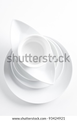 A stack of clean white different dishes on a white background - stock photo