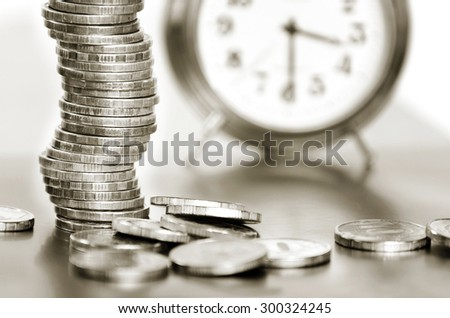 A stack of coins and alarm clock black and white - stock photo