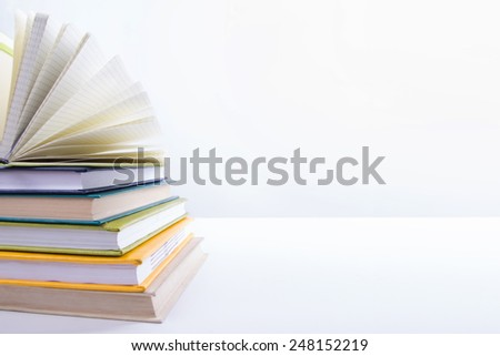 A stack of colorful books and open book. Ideas for business and self-development isolated on white background. Empty space