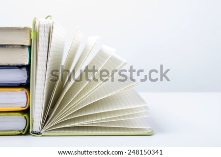 A stack of colorful books and open book. Ideas for business and self-development. Study background. - stock photo