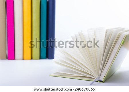 A stack of colorful books, open book. - stock photo
