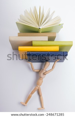A stack of colorful books, open book. Wooden mannequin tries to get up the stack of colorful books. - stock photo