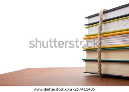 A stack of colorful books tied with a rope on white background, copy space for text, back to school. - stock photo